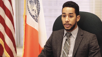 NYC Council Member Antonio Reynoso sitting at his desk, with the American and NYC City flags to his right.